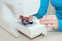 Το καυκάσιο κορίτσι παρεμβάλλει ένα μασούρι με το νήμα στη ράβοντας μηχανή στοκ φωτογραφία με δικαίωμα ελεύθερης χρήσης