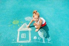 Το καυκάσιο μικρό κορίτσι της Νίκαιας σύρει την εικόνα σπιτιών κιμωλίας Στοκ Φωτογραφία