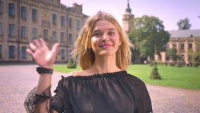 Το καυκάσιο ξανθό κορίτσι Smiley αρκετά στέκεται και κυματίζει στη κάμερα, καταψύχοντας στην οδό, συμπαθητικός ηλιόλουστος καιρός απόθεμα βίντεο