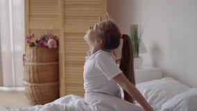 Το καυκάσιο παιδί χαριτωμένο χαλαρώνει ή κορίτσι παιδιών ξυπνήστε ή ξύπνησε με το τέντωμα οι ίδιοι μετά από τον ύπνο για να αναζω απόθεμα βίντεο