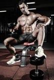 Το καυκάσιο προκλητικό αρσενικό πρότυπο ικανότητας εκτελεί την άσκηση με τον αλτήρα Στοκ Φωτογραφίες