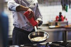 Το καυκάσιο χέρι αρχιμαγείρων χύνει το φυτικό έλαιο σε μια παν πλάγια όψη τηγανίσματος Στοκ Φωτογραφία