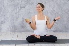Το καυκάσιο όμορφο υγιές αθλητικό αθλητικό κορίτσι τρώει το πράσινο μήλο μετά από την κατάρτιση και την εξέταση τη κάμερα Στοκ Εικόνες