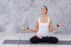 Το καυκάσιο όμορφο υγιές αθλητικό αθλητικό κορίτσι τρώει το πράσινο μήλο μετά από την κατάρτιση και την εξέταση τη κάμερα Στοκ φωτογραφίες με δικαίωμα ελεύθερης χρήσης