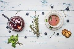 Το καυτό βοτανικό τσάι με τη μέντα, η μαρμελάδα του κυμινοειδούς κάρου από ένα τριαντάφυλλο, και τα μπισκότα, σε ένα ξύλινο αγροτ Στοκ φωτογραφίες με δικαίωμα ελεύθερης χρήσης