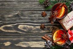 Το καυτό θερμαμένο κρασί Χριστουγέννων με το δέντρο κανέλας, γλυκάνισου και έλατου διακλαδίζεται με τα κιβώτια δώρων Στοκ εικόνες με δικαίωμα ελεύθερης χρήσης