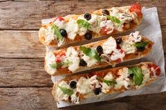 Το καυτό νόστιμο baguette περικοπών έψησε με το κοτόπουλο, τυρί, ντομάτες, oli Στοκ Φωτογραφία