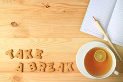 Το καυτό τσάι λεμονιών, τα έγγραφα σημειώσεων και το μολύβι εκτός από με το Word ΠΑΙΡΝΟΥΝ μια ορθογραφία ΣΠΑΣΙΜΑΤΩΝ με τα μπισκότ Στοκ Εικόνες