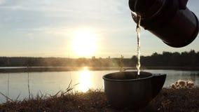 Το καυτό τσάι χύνεται από μια φιάλη σε ένα φλυτζάνι σε μια τράπεζα λιμνών στην slo-Mo απόθεμα βίντεο