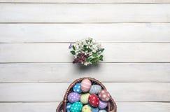 Το καλάθι με τα ζωηρόχρωμα αυγά Πάσχας, που χρωματίζονται σε χειροποίητο και μια ανθοδέσμη των λουλουδιών άνοιξη στέκονται σε μια Στοκ φωτογραφίες με δικαίωμα ελεύθερης χρήσης