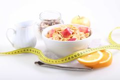 Το καλαμπόκι και το ρύζι ξεφλουδίζουν με ένα φρέσκο μήλο, ένα πορτοκάλι και ένα measuri Στοκ Φωτογραφία