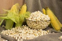 Το καλαμπόκι στο σπάδικα και popcorn σε ένα γυαλί κυλούν στον πίνακα Στοκ εικόνα με δικαίωμα ελεύθερης χρήσης