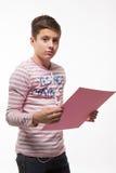 Το καλλιτεχνικό brunette αγοριών εφήβων σε έναν ρόδινο άλτη με ένα ρόδινο φύλλο του εγγράφου για τις σημειώσεις Στοκ φωτογραφία με δικαίωμα ελεύθερης χρήσης