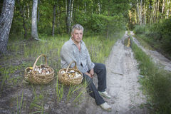 Το καλοκαίρι, ένα άτομο με δύο καλάθια των μανιταριών κάθεται Στοκ εικόνα με δικαίωμα ελεύθερης χρήσης