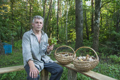 Το καλοκαίρι, ένα άτομο με δύο καλάθια των μανιταριών κάθεται Στοκ φωτογραφία με δικαίωμα ελεύθερης χρήσης