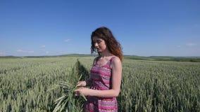 Το καλοκαίρι, μεταξύ του τομέα σίτου, μια νέα γυναίκα, κλαίει ένα στεφάνι των αυτιών απόθεμα βίντεο