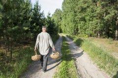 Το καλοκαίρι στο δάσος κατά μήκος του δρόμου είναι άτομο με δύο καλάθια Στοκ φωτογραφία με δικαίωμα ελεύθερης χρήσης