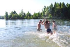 Το καλοκαίρι, τα αγόρια κολυμπούν στη λίμνη, κατάδυση, παφλασμός στοκ εικόνα