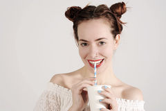 Το καλό νέο κορίτσι πίνει με ένα άχυρο με το αθώο χαμόγελο στο πρόσωπό της Στοκ Φωτογραφία