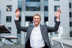 Το καλύτερο πλήρες μήκος ημέρας πάντα του ευτυχούς νέου επιχειρηματία στην επίσημη κράτηση ένδυσης οπλίζει αυξημένος και εκφράζον Στοκ Φωτογραφίες