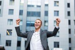 Το καλύτερο πλήρες μήκος ημέρας πάντα του ευτυχούς νέου επιχειρηματία στην επίσημη κράτηση ένδυσης οπλίζει αυξημένος και εκφράζον Στοκ εικόνες με δικαίωμα ελεύθερης χρήσης