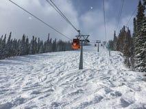 Το καλώδιο ανυψώνει σε έναν κασσίτερο χιονοδρομικών κέντρων τον ηλιόλουστο καιρό Στοκ Εικόνες