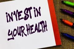 Το κείμενο γραφής επενδύει στην υγεία σας Η έννοια έννοιας ζει υγιή ποιοτικά τρόφιμα τρόπου ζωής για το ανοικτό σημειωματάριο Wel στοκ εικόνα