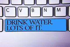 Το κείμενο γραφής πίνει το νερό Μέρη από το Έννοια που σημαίνει πίνοντας τα υγρά για να κρατήσει το σώμα μας στο μεγάλο blu κουμπ Στοκ εικόνες με δικαίωμα ελεύθερης χρήσης