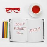 Το κείμενο δεν ξεχνά να χαμογελάσει γραπτός σε ένα σημειωματάριο Στοκ Εικόνες