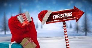 Το κείμενο και τα δώρα Χριστουγέννων με ξύλινο καθοδηγούν στο χειμερινό τοπίο Χριστουγέννων και το καπέλο Santa με το Chris Στοκ φωτογραφίες με δικαίωμα ελεύθερης χρήσης