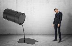 Το κεκλιμένο βαρέλι με τη μαύρη υγρή έκχυση πετρελαίου έξω από το επάνω και ο λυπημένος επιχειρηματίας Στοκ φωτογραφία με δικαίωμα ελεύθερης χρήσης