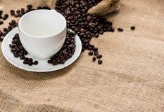 Το κενά φλυτζάνι καφέ και τα φασόλια καφέ sackcloth έχουν το έτοιμο fil Στοκ Εικόνα
