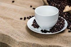 Το κενά φλυτζάνι καφέ και τα φασόλια καφέ sackcloth έχουν το έτοιμο fil Στοκ Φωτογραφίες