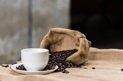 Το κενά φλυτζάνι καφέ και τα φασόλια καφέ sackcloth έχουν το έτοιμο fil Στοκ φωτογραφίες με δικαίωμα ελεύθερης χρήσης