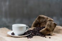 Το κενά φλυτζάνι καφέ και τα φασόλια καφέ sackcloth έχουν το έτοιμο fil Στοκ φωτογραφία με δικαίωμα ελεύθερης χρήσης