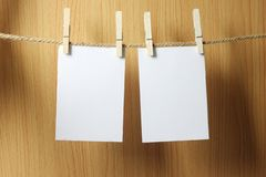 Το κενό έγγραφο κρεμά στο καφετί σχοινί με τους ξύλινους συνδετήρες εγγράφου στο W στοκ φωτογραφίες