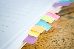Το κενό βιβλίο σημειώσεων με το colorfull το ταχυδρομεί στον ξύλινο πίνακα Στοκ εικόνα με δικαίωμα ελεύθερης χρήσης