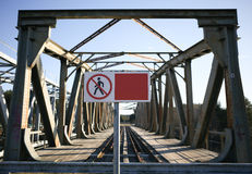 Το κενό κενό έμβλημα μπροστά από τον παλαιό σιδηρόδρομο δεν γεφυρώνει κανένα trespassin Στοκ Εικόνα
