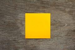 Το κενό πορτοκαλί έγγραφο σημειώσεων συνδέει στο καφετί ξύλινο υπόβαθρο στοκ φωτογραφίες