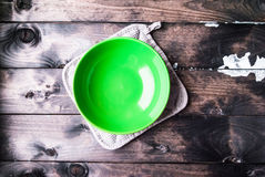 Το κενό πράσινο κύπελλο βρίσκεται σε ένα γκρίζο potholder Στοκ Φωτογραφία