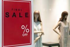 Το κενό σημάδι πώλησης με το διάφορο ποσοστό υπογράφει στο κόκκινο υπόβαθρο στο μέτωπο τα θηλυκά μανεκέν στο κατάστημα μόδας στοκ εικόνα
