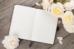 Το κενό σημειωματάριο και άσπρος αυξήθηκε λουλούδια Στοκ φωτογραφία με δικαίωμα ελεύθερης χρήσης
