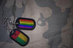 το κενό στρατού, η ετικέττα σκυλιών με τη σημαία της Γουινέα-Μπισσάου και το ομοφυλοφιλικό ουράνιο τόξο σημαιοστολίζουν στο χακί  Στοκ Εικόνες