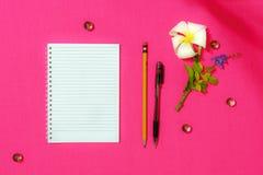 Το κενό φύλλο του σημειωματάριου με τη μάνδρα, το μολύβι και το frangipani ανθίζουν στο κόκκινο υπόβαθρο για κάποιο ιδέα ή μήνυμα Στοκ Εικόνες