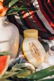 Το κεραμικό βάζο, κέρατα, τεμάχισε τα πεπόνια και τα φύλλα καρπουζιών και φοινικών σε ένα υπόβαθρο του κόκκινου υφάσματος προσθηκ Στοκ Φωτογραφίες