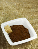 Το κεραμικό κύπελλο με τον επίγειο καφέ και η καφετιά ζάχαρη κυβίζουν στο υπόβαθρο σάκων σύστασης Στοκ Φωτογραφία
