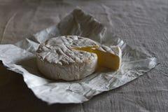 Το κεφάλι του ελβετικού Camembert τυριού και ένα κομμάτι του τυριού σε ένα υφαμένο υπόβαθρο καμβά Στοκ εικόνες με δικαίωμα ελεύθερης χρήσης