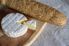 Το κεφάλι του ελβετικού Camembert τυριού και ένα τριγωνικό κομμάτι του τυριού σε έναν ξύλινο πίνακα και ενός baguette σιταριού υφ Στοκ Εικόνες
