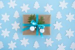 Το κιβώτιο δώρων που τυλίγεται του εγγράφου τεχνών, της μπλε κορδέλλας και του διακοσμημένου έλατου διακλαδίζεται και ασημένιες σ Στοκ εικόνα με δικαίωμα ελεύθερης χρήσης