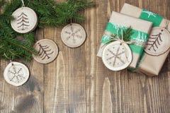 Το κιβώτιο δώρων Χριστουγέννων στο αγροτικό ύφος τύλιξε στο έγγραφο με το ντεκόρ ξύλινου που τεμαχίστηκε με το σύμβολο στοκ εικόνα με δικαίωμα ελεύθερης χρήσης